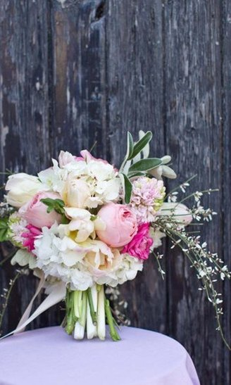 wedding bouquet comprised of round pink and white flowers mixed with purple and white flowers mixed with green leaves