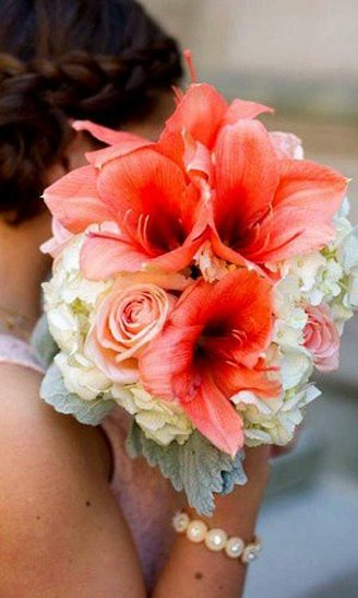 A beautiful bouquet consisting of white and red flowers, mixed with grey leaves held by the bride