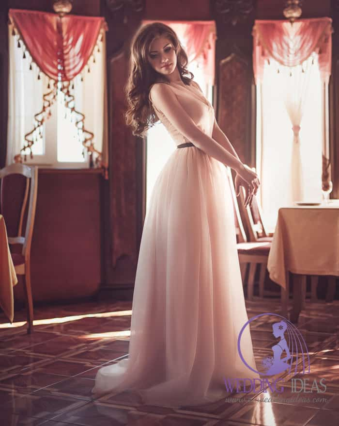 V-neck necklace with dark belt in the waist, long skirt. Straight but very elegant wedding dress. Long brown curly hair and no-makeup look.