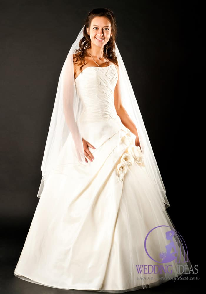 Ball gown with a straight neckline and two flowers and a little bit of tulle in the skirt