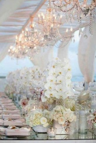 A romantic pink wedding tent with matching seats, table clothes and flowers. It also has matching lights