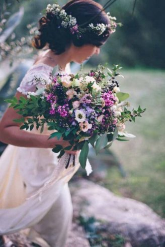 A beautiful wedding bouquet made of green leaves and white, purple and blue flowers
