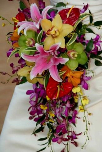 A lovely bouquet consisting of yellow, purple, green and red flowers and strings of green leaves held by the bride