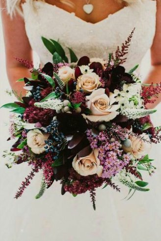 A fabulous wedding bouquet consisting of white, red and green flowers and grey fruits