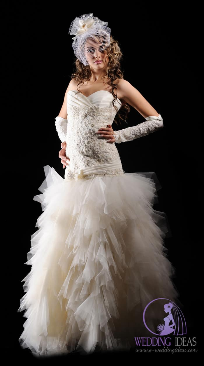 Strapless sweetheart necklace, lace design with jewelry on the bodice. Layered, long tulle skirt.