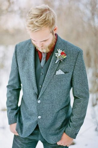 A groom in a grey blazer, grey sleeveless blazer, maroon shirt, grey tie, grey jeans, grey pocket square and a green, red and grey boutonniere
