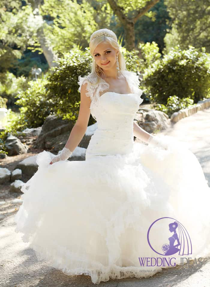 Ball gown wedding dress with a straight neckline. Lace straps and lace design on the bodice.