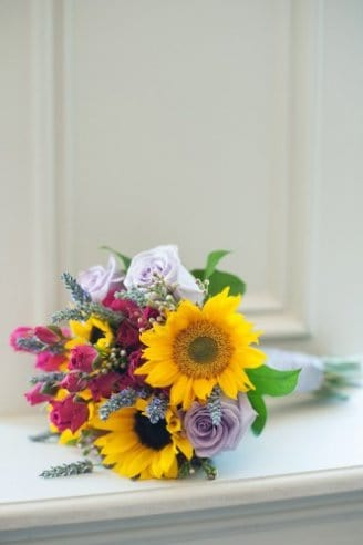 A small wedding bouquet consisting of yellow, black, purple, white and green flowers