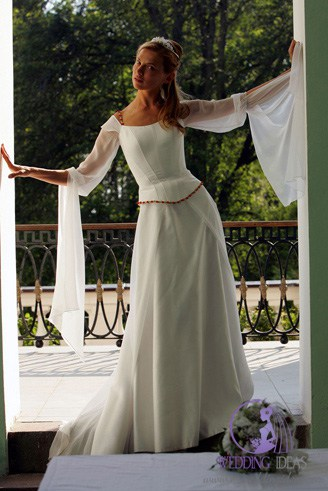 A white, gown with long, exaggerated sleeves and a jewel-shaped bust