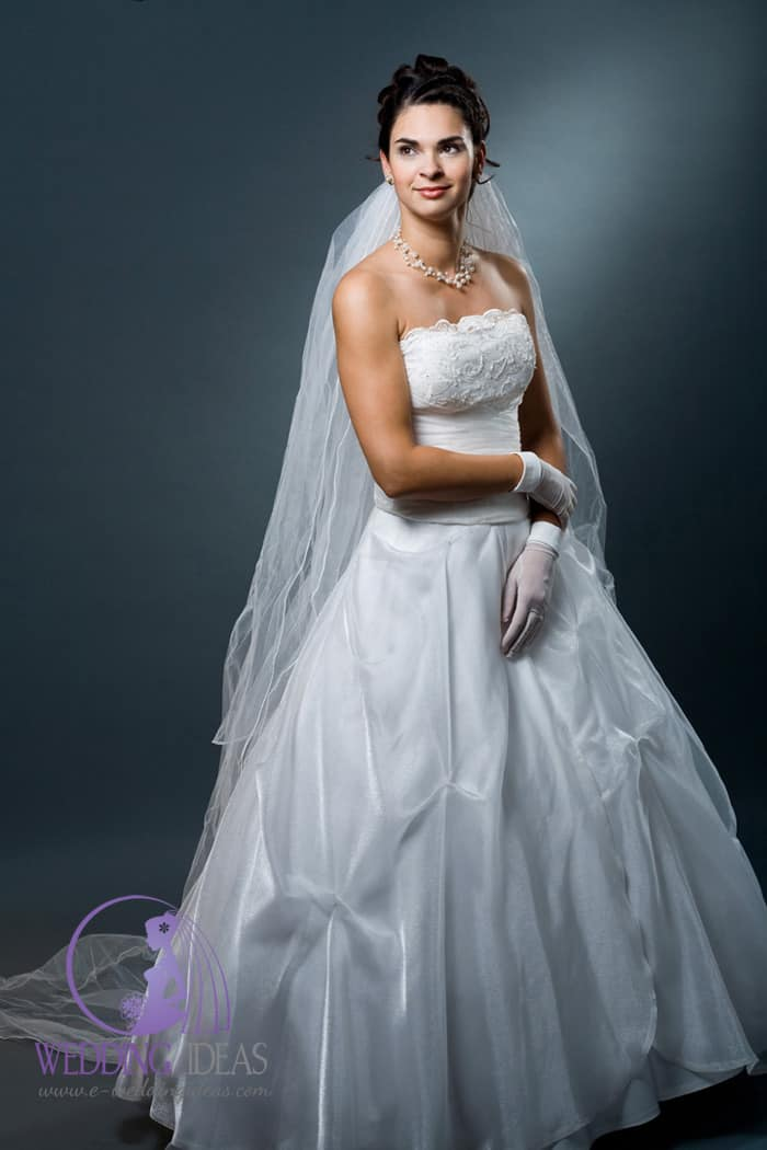 Ball gown with a straight necklace. Lace design on the bust, pleated in the waist