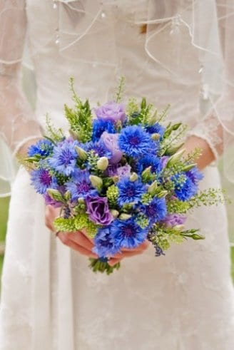 A beautiful bridal bouquet made of green leaves and white, purple and blue flowers