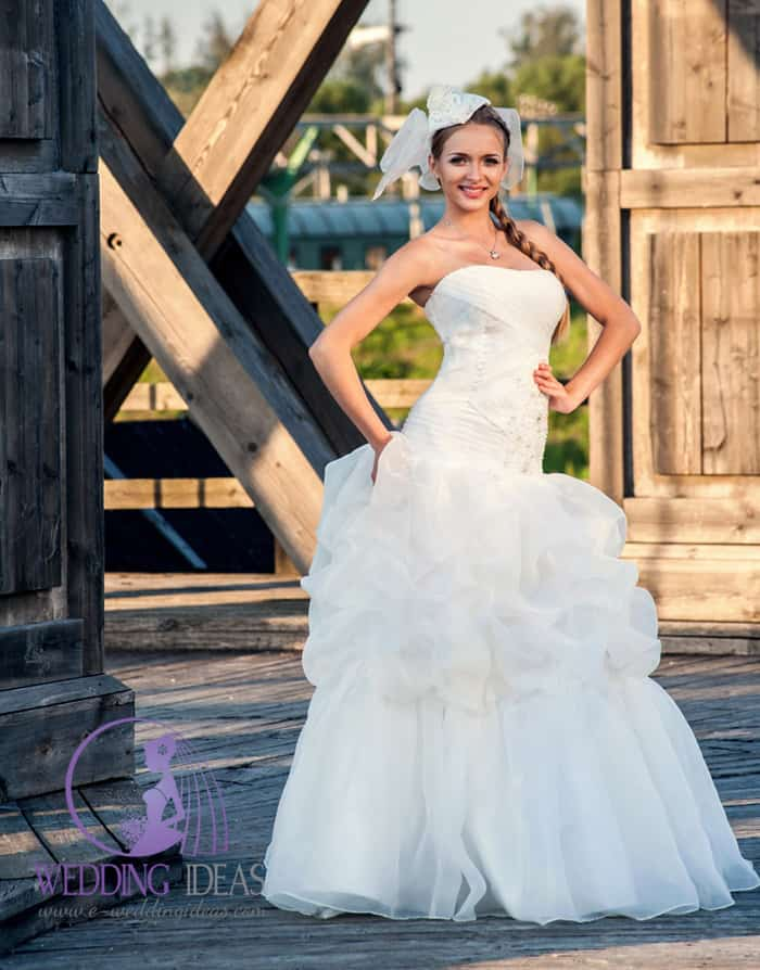 Ball gown wedding dress with straight necklace. Pleated bodice with lace design on the left side.