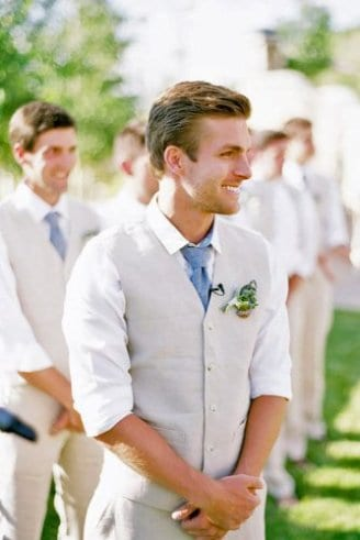 A groom in a grey sleeveless blazer, white shirt, blue tie and a white and green boutonniere