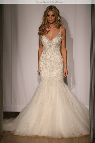 A mermaid wedding dress with spaghetti straps. It is also very wide at the bottom.