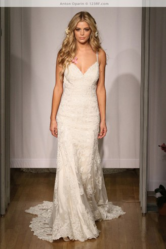 A white, fitting bridal dress with spaghetti straps and a rough texture