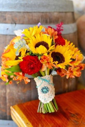 A romantic bouquet made of round red and green flowers mixed with sunflowers and tied with a white and blue ribbon