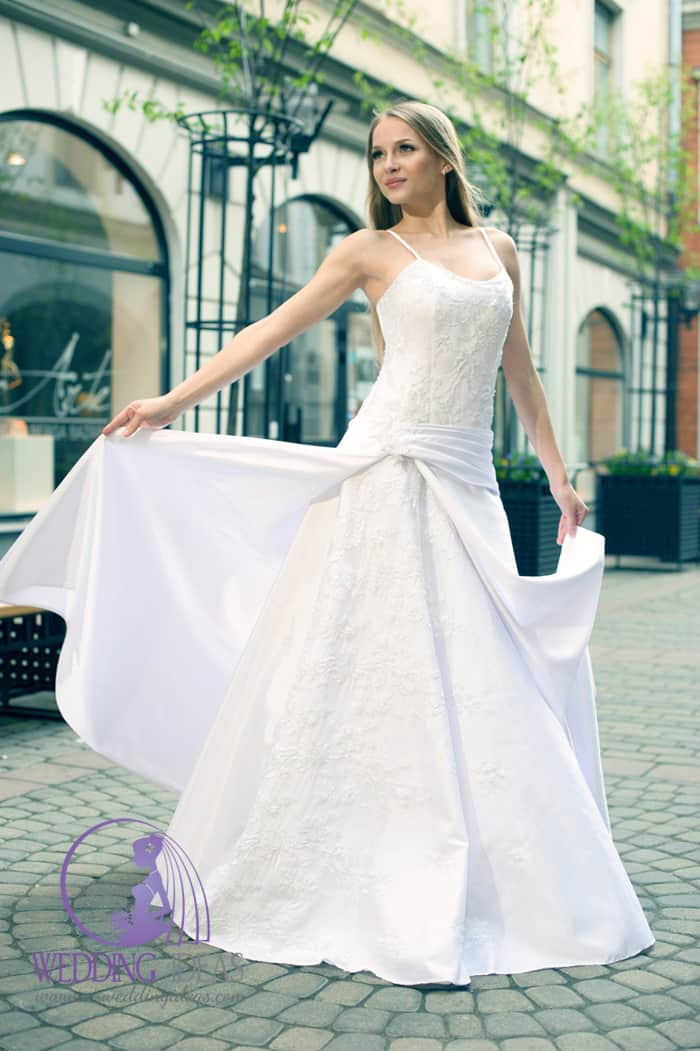 Spaghetti strap and lace bodice. Satin belt on the hip and one satin layer on the skirt, make from lace. Blond hair and delicate make up.