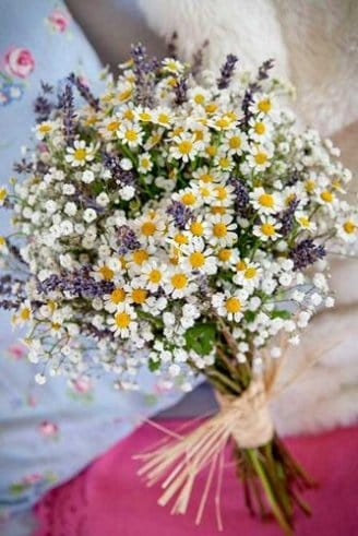 A beautiful wedding bouquet made of small round white, purple and yellow flowers