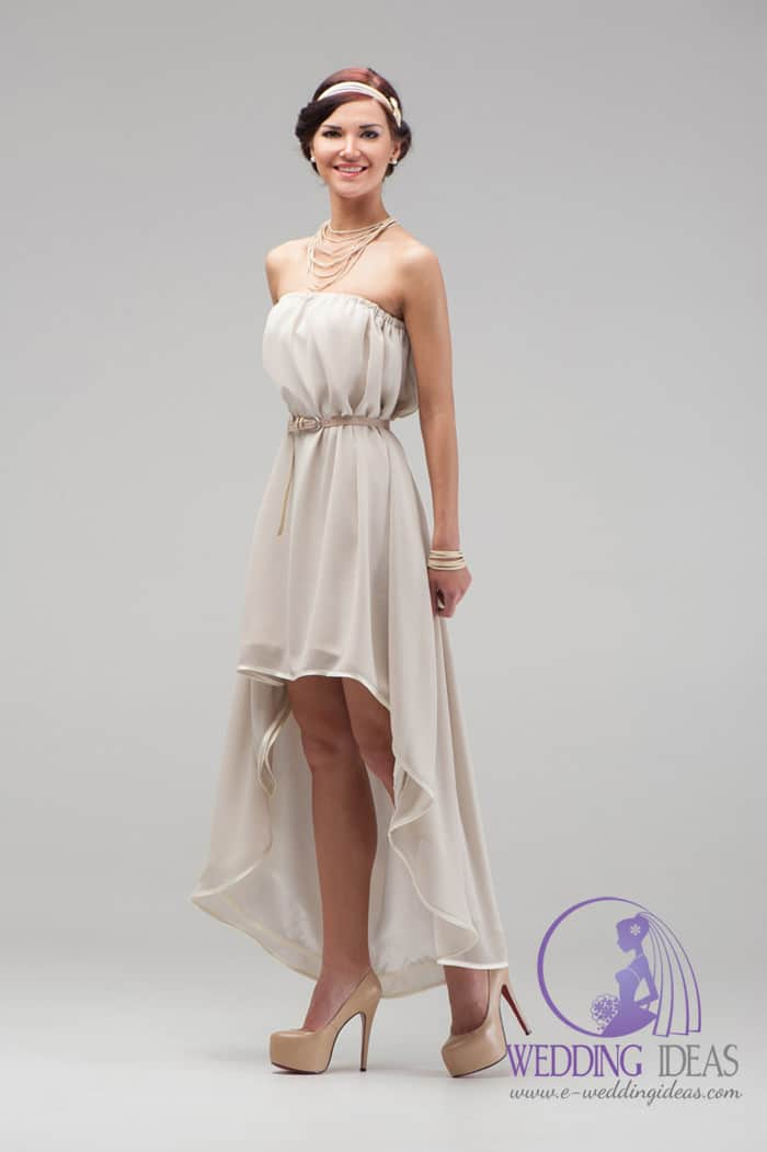 75. Hi-low beige wedding dress with straight necklace. Vintage look with belt in the waist. White hairband in the brown hair. Elegant jewellery and nude high heels.