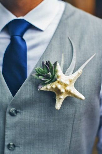 A groom in a grey sleeveless blazer, blue shirt, navy blue tie and a cream and green boutonniere