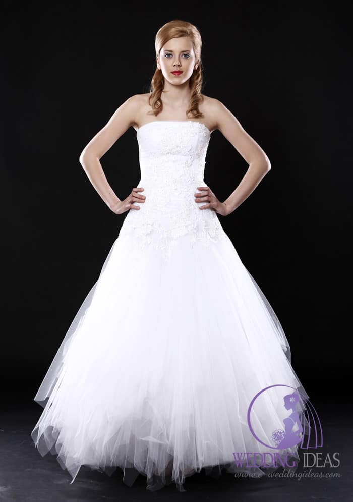 8. Bride dress straight lace necklines with floral accent and tulle skirt. Red lips is only makeup what we can see. A black wall like open-air shows all details off the gown.