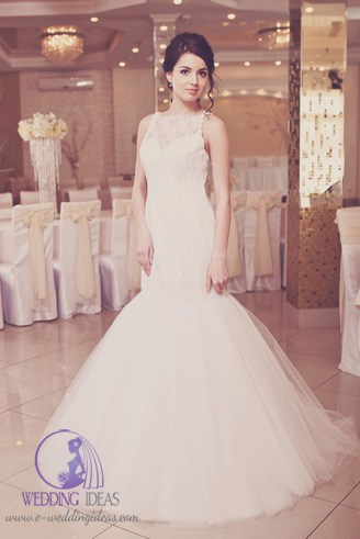 A white, fitting dress with spaghetti straps and rough texture and a very wide base