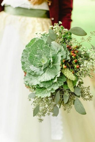 A lovely wedding bouquet made of round green kales, green fruits, and small white and green flowers