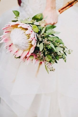 A romantic wedding bouquet comprised of a big round pink flower mixed with green leafy flowers
