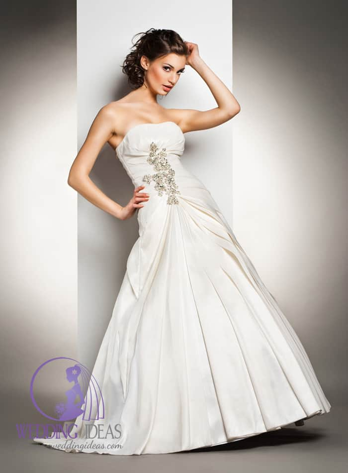 88. Ball gown with straight necklace and crystals on the bodice. Long pleated skirt. Pinned up brown curly hair and delicate natural make up.