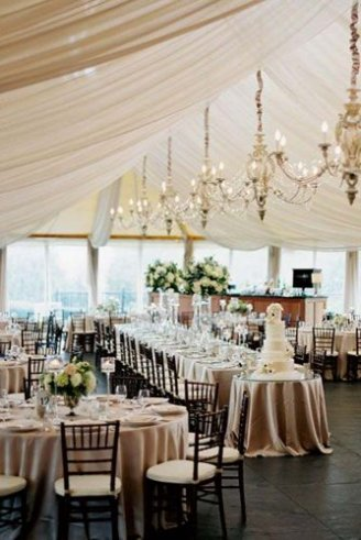 A romantic white wedding tent with pink seats, matching table clothes and pink flowers.