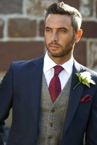 A groom in a black blazer, grey sleeveless blazer, white shirt, maroon tie, maroon pocket square and a white and green boutonniere