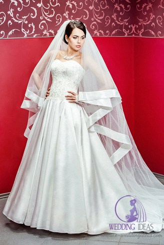 A white bridal gown with a sweetheart-shaped bust and a long veil.