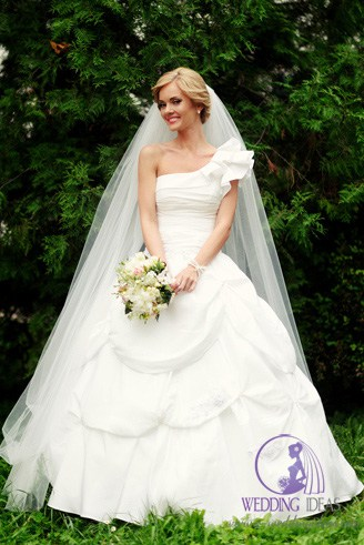 A white bridal dress with an asymmetric bust. It is wide at the bottom and has a matching head gear.