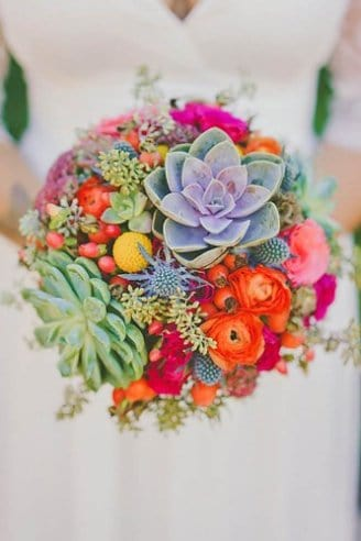 A lovely wedding bouquet consisting of blue, yellow, pink and red flowers and green succulent flowers held by the bride