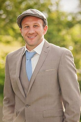 A bridegroom in a grey three-piece suit white shirt, blue tie, and a brown cap