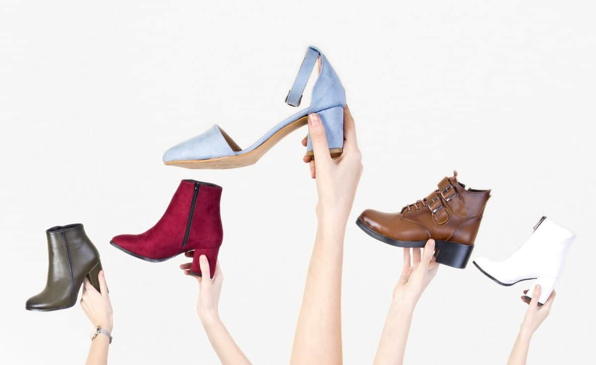 Hands holding different woman shoes on white isolated background. Close up.