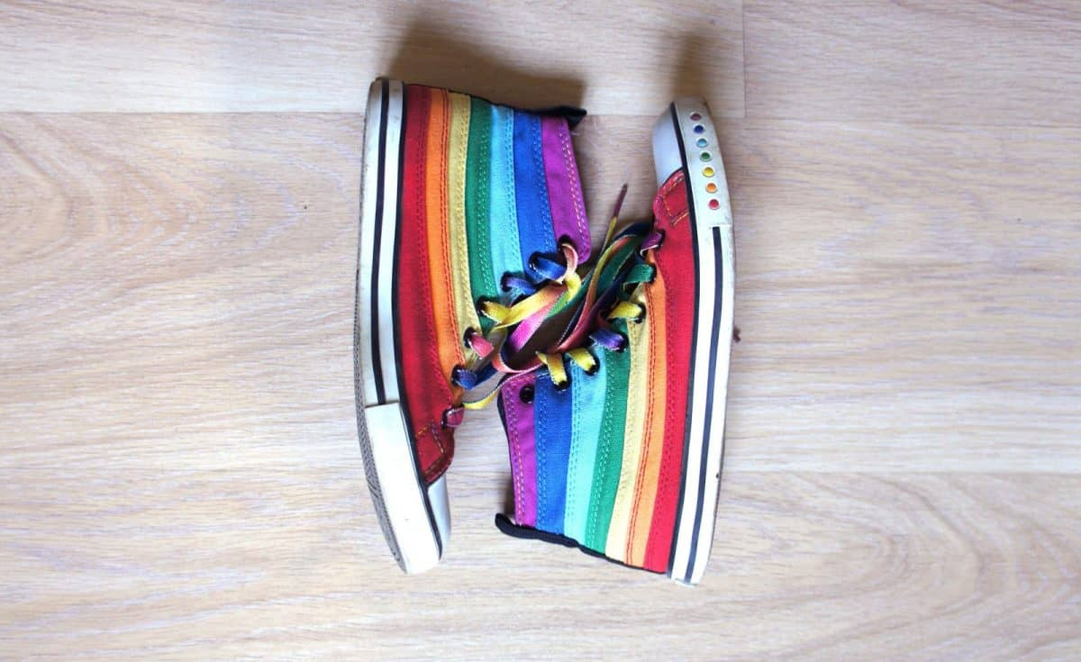 Sneakers LGBT colors. Fashionable shoes on wooden background. top view.
