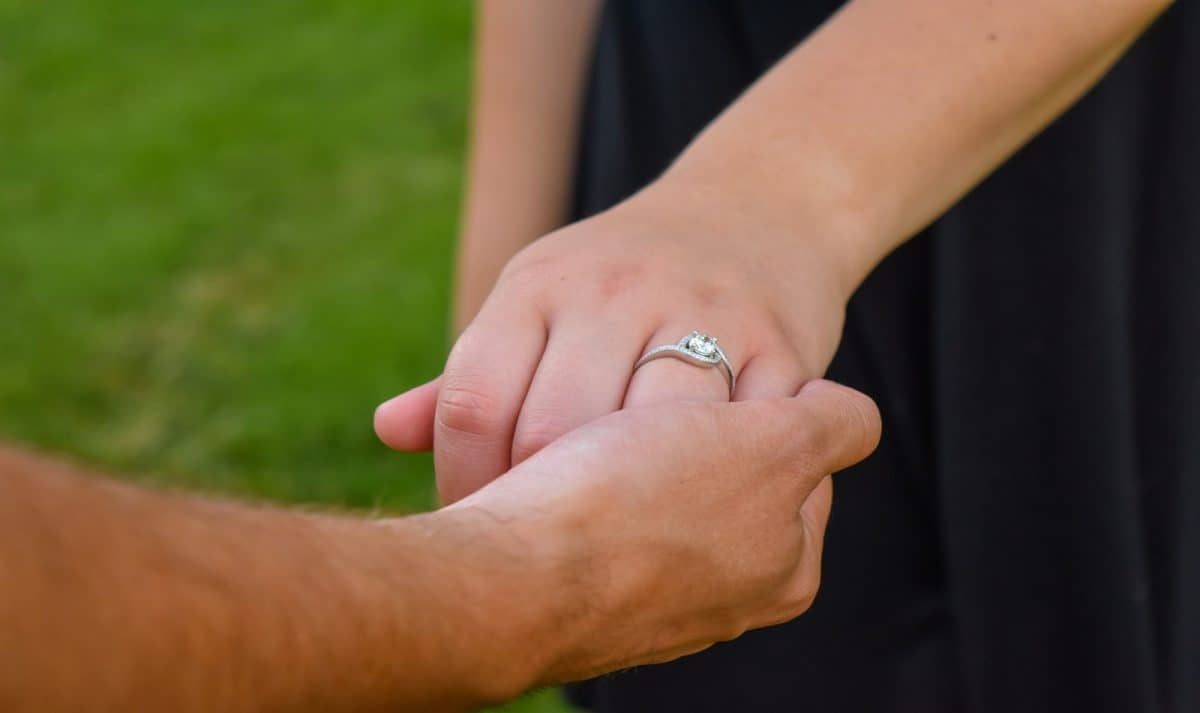 a man holding his fiancée's hand with an engagement ring