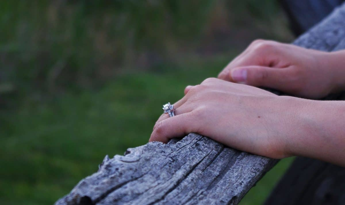 a girl's hand wearing an engagement ring holding a wood fence