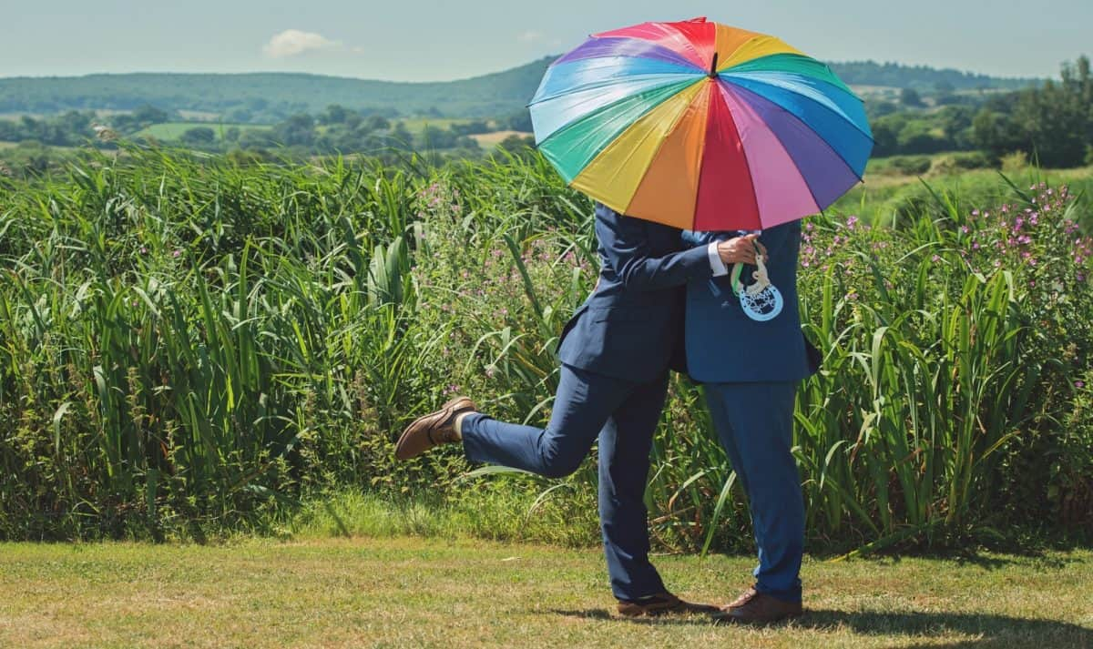 gay couple holding a rainbow umbrella on a grass field