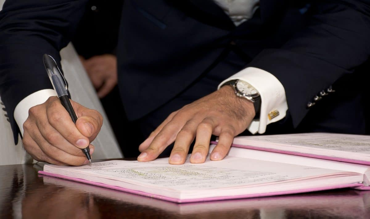 groom signing his marriage contract after a surprise wedding