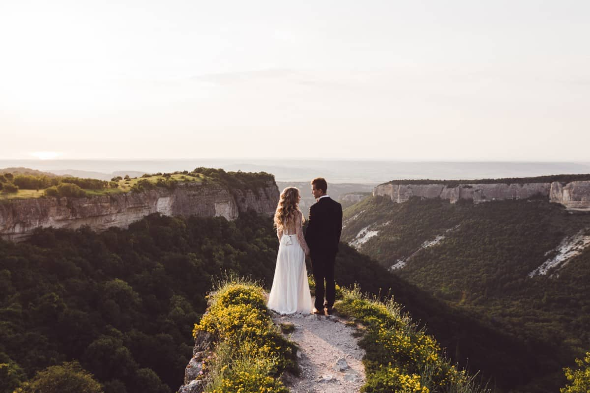 a scenic view of a groom and bride on top of the mountains as they best alternative wedding option