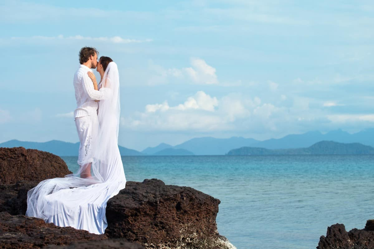 groom and bride kissing on top of a cliff surrounded by the sea