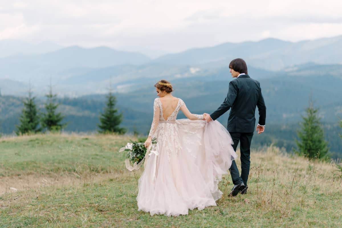 a bride and groom walking on top of a mountain, one of the best alternative wedding options