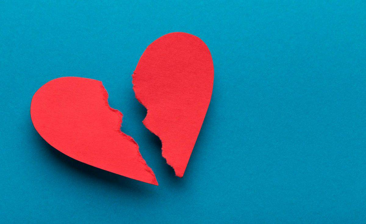 red paper broken heart on a blue background