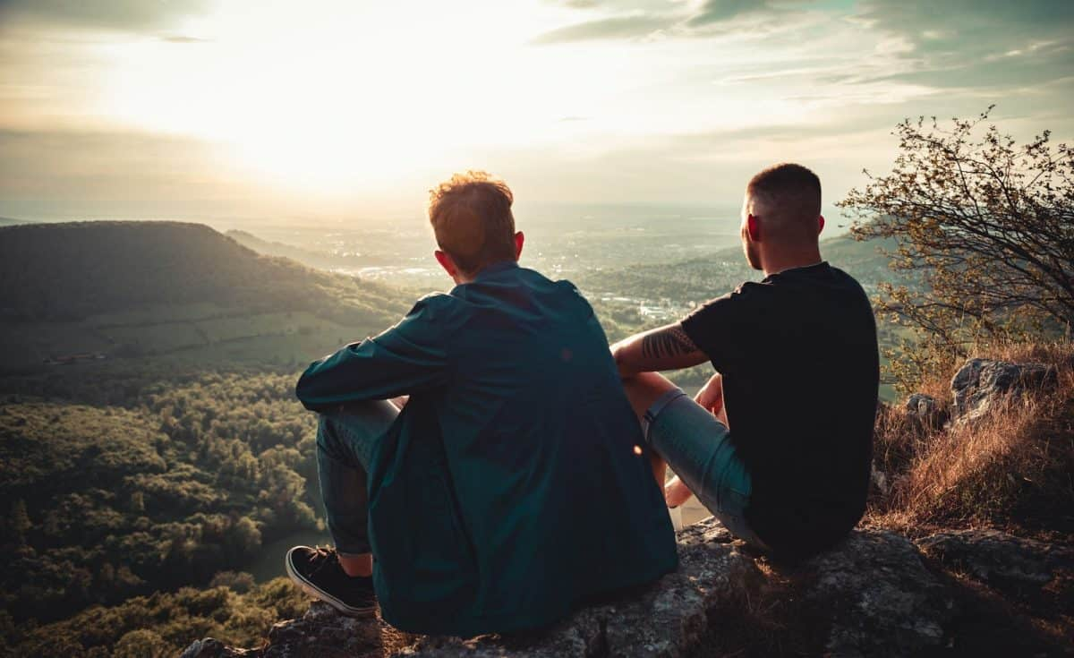 gay couple sitting together side by side on Mountain Top during sunset. Looking down to the valley, enjoying the sunset mood and view together. Millennial Generation Real People Outdoor Nature Lifestyle.