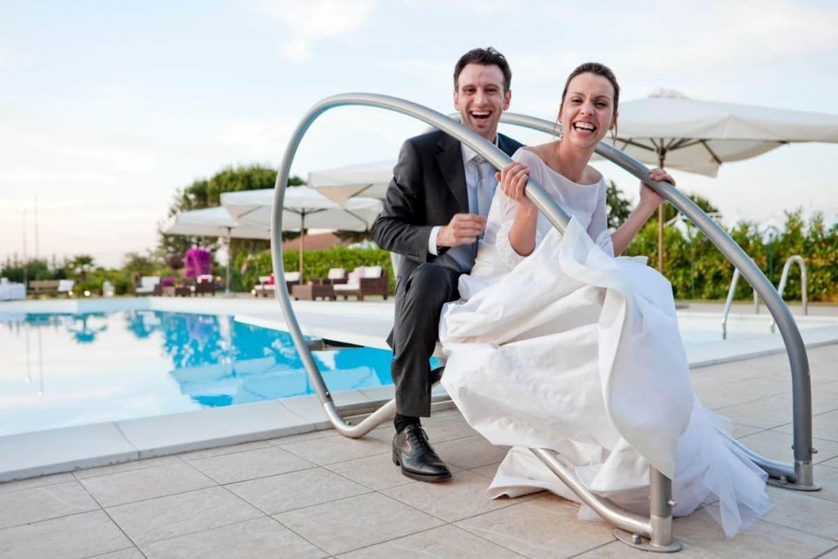 bride and groom having fun at the swimming pool