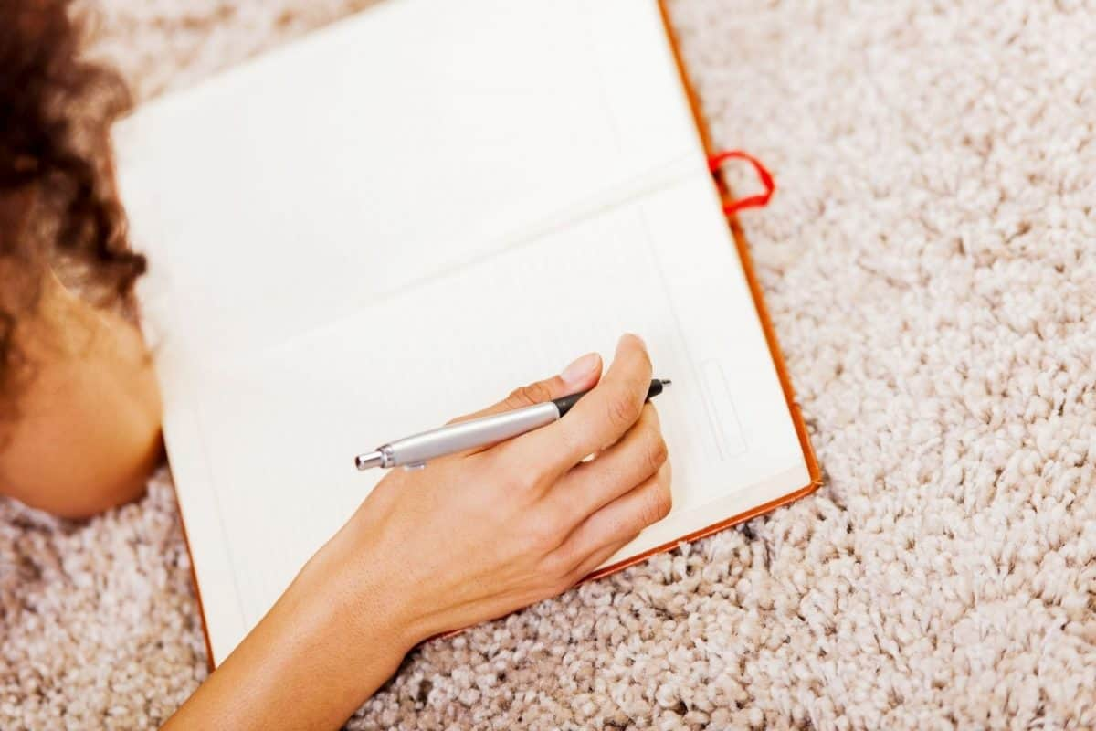 a lady thinking how to write a lesbian wedding officiant speech on her notebook
