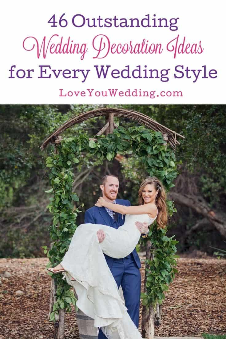 groom carrying his bride in front of a post decorated with leaves