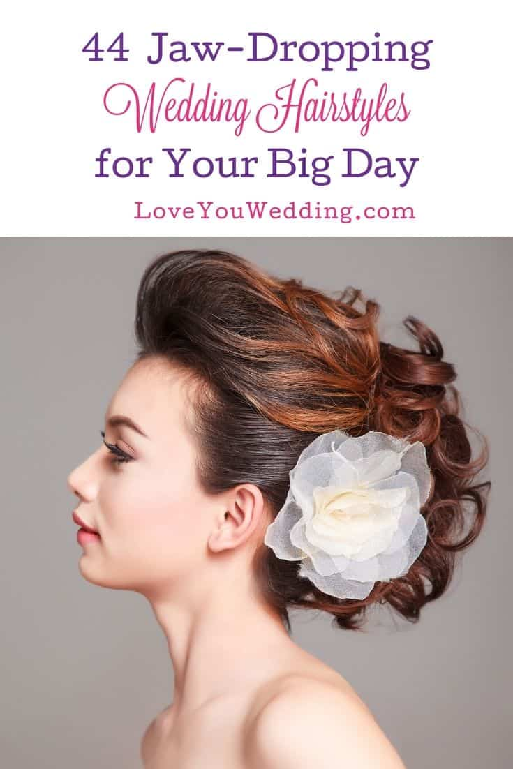 a gorgeous bride with a curly bun pinned with a big white flower hairstyle